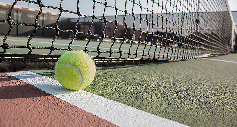 Tennis ball on court next to net