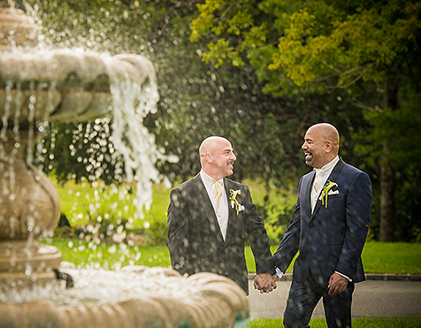Two groomsmen by water fountain