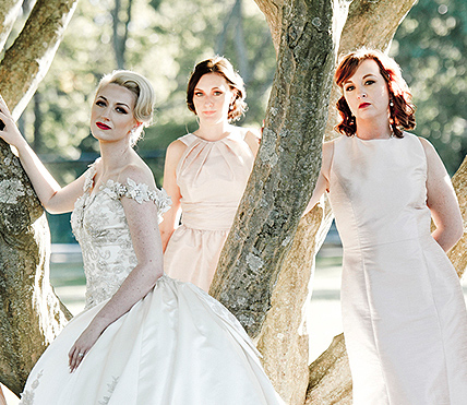 Three women in ivory dresses by tree