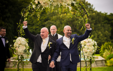 Two men standing under wedding arc