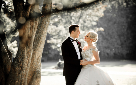 Wedding couple standing under tree