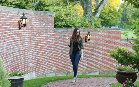 Woman walking by brick wall surrounded by greenery