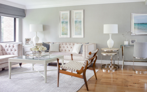 Clean and modern living space with white leather couches, glass coffee table & white decor