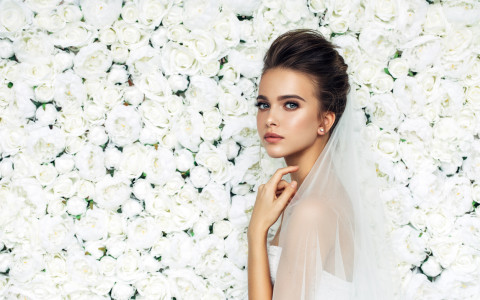 bride with veil in front of white roses
