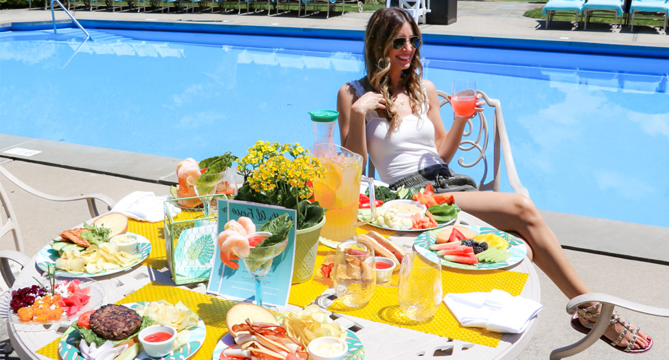 woman sitting at a table full of food next to the pool