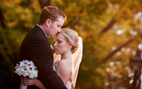 Groom kissing brides forehead in a garden