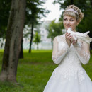Blonde bride in white wedding dress holding a white dove on green grass next to trees