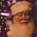 Santa Claus with white beard and red and white hat surrounded by Christmas Lights