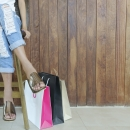 Woman with Legs Crossed with 2 Shopping Bags