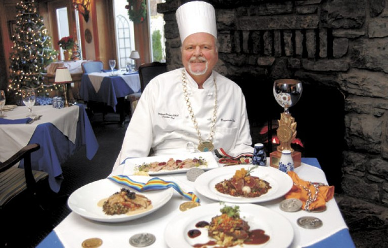 Chef sitting next to table of prepared food