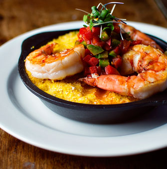 Jumbo shrimp on polenta topped with mixed bell peppers