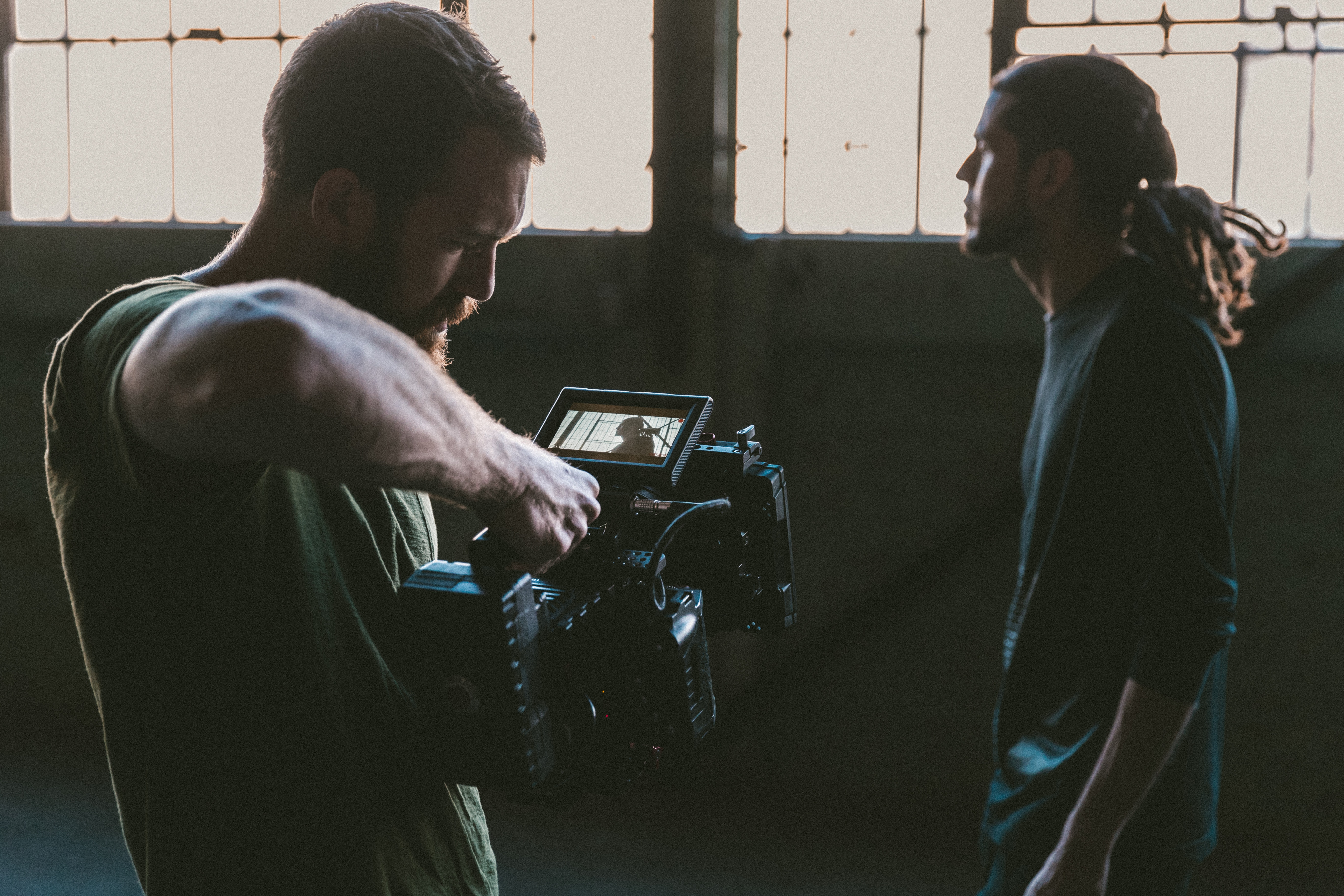 One man filming another in a warehouse