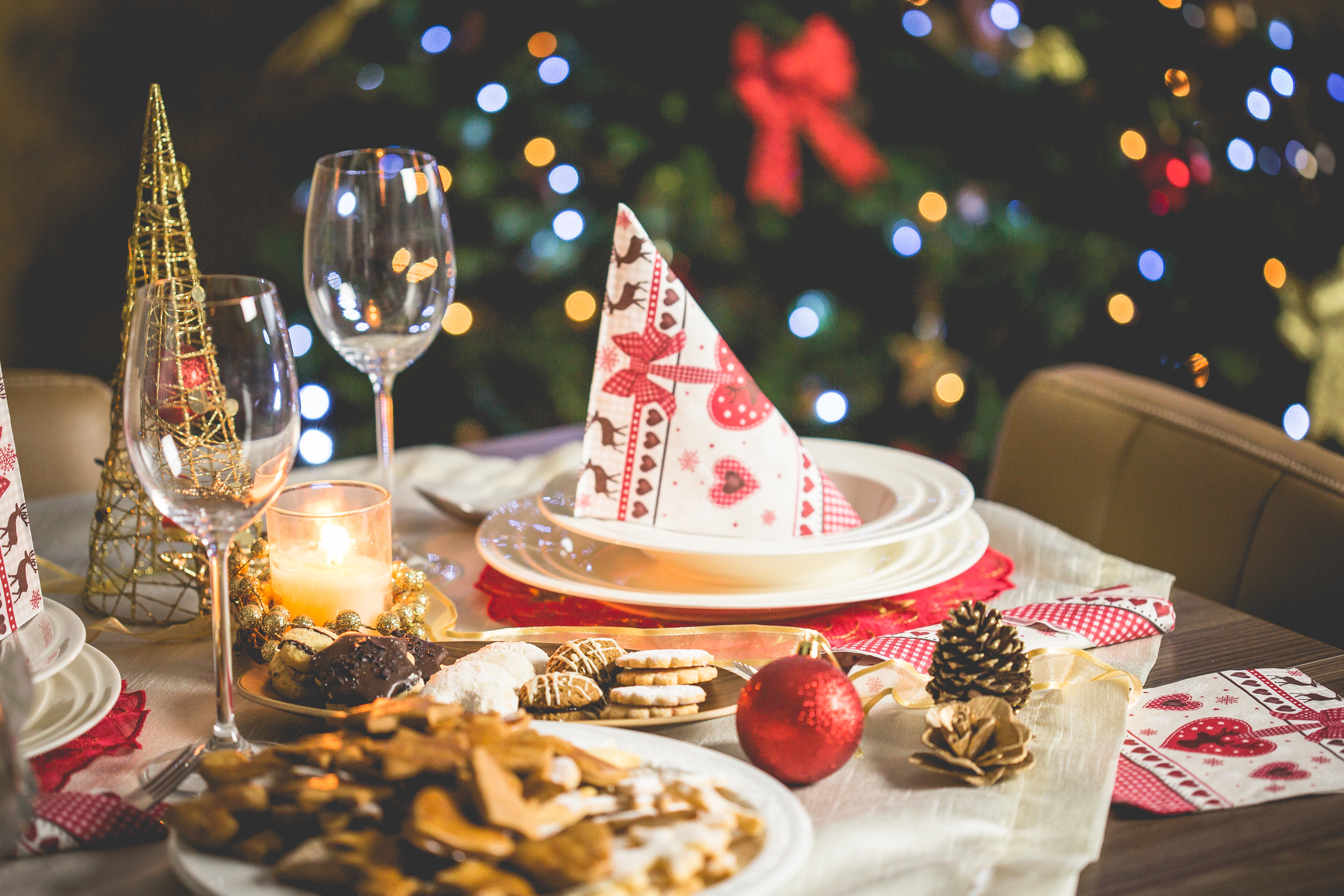 Table set with cookies and various Christmas decor along with Christmas tree in background