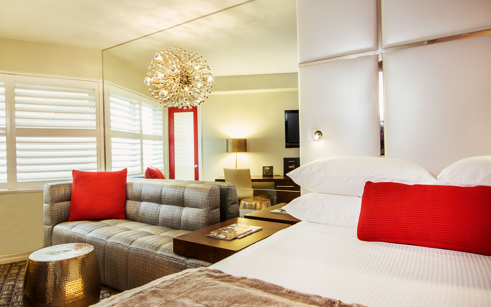 White bed with red pillows and mirrored wall
