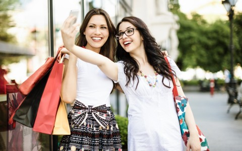 two young woman shopping laughing and taking photos on cell phones