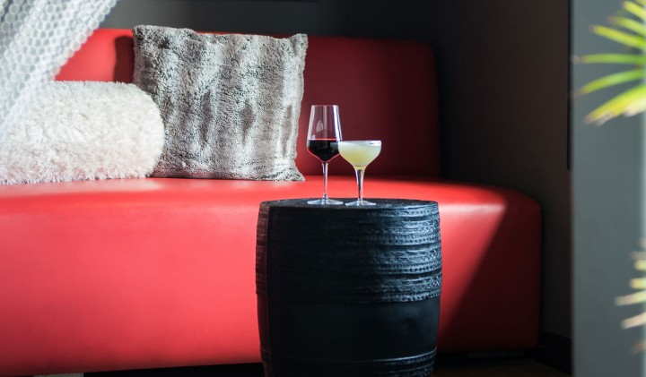shot of the red couch in the grafton lobby with a margarita and glass of red wine