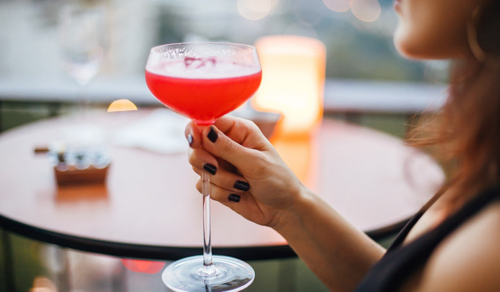 woman holding a red colored cocktail at a table overlooking a balcony