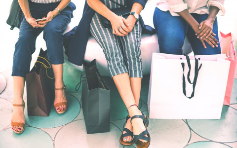 Three women sitting with shopping bags photographed from waist down