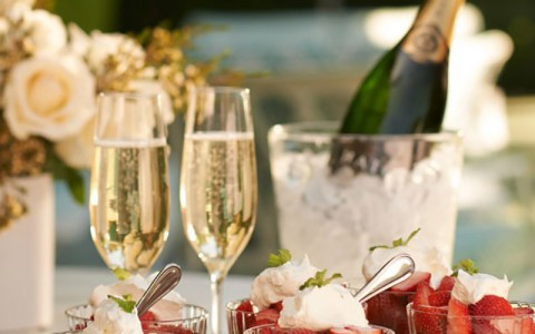 romantic set up of champagne and a strawberry dessert