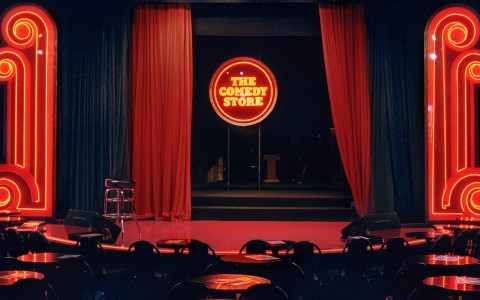 the dark red and black stage at the comedy store