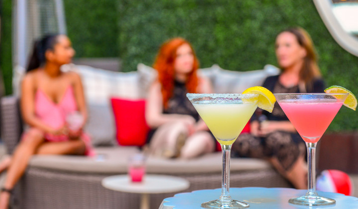 three young women on a couch out by the pool with two martinis in the foreground