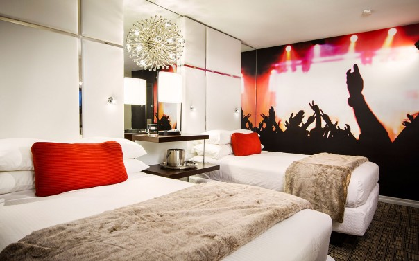 double beds with concert mural on the wall and crystal chendelier