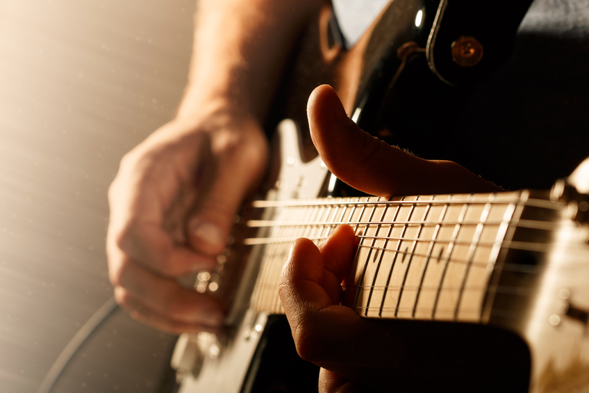 close up of someone playing guitar