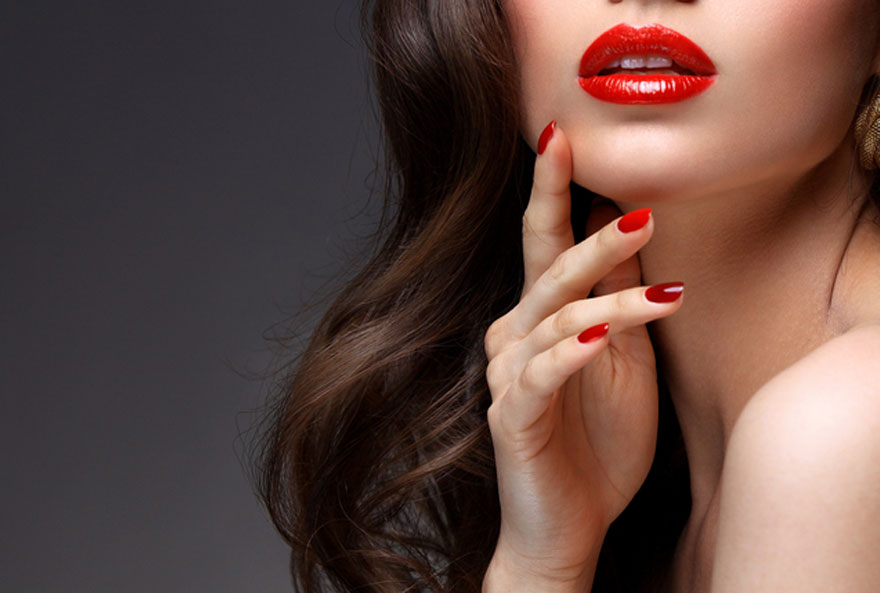 close up of model with red lipstick and red nails