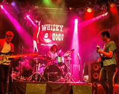 Band performing on stage with pink neon lights at Whisky A Go Go