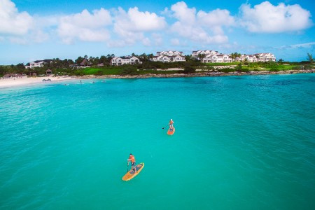 blue ocean with two people paddle boarding