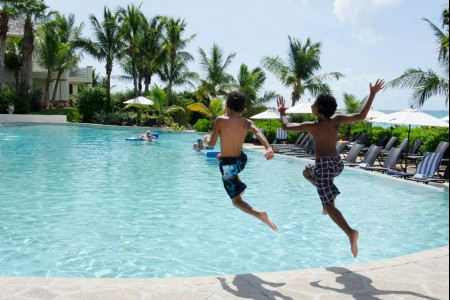 two boys jumping into the pool