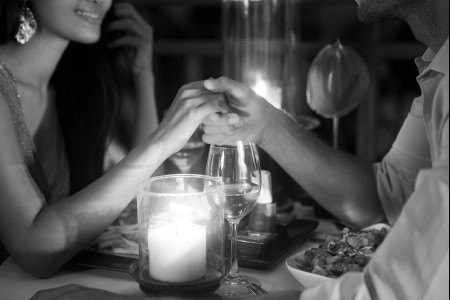 a couple holding hands over dinner