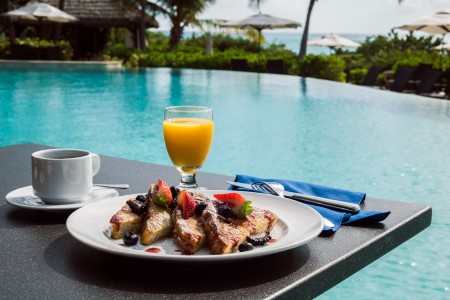 close up of french toast and orange juice next to the pool