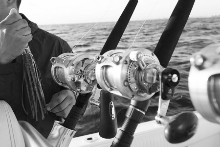 close up of fishing poles with ocean in background in black and white