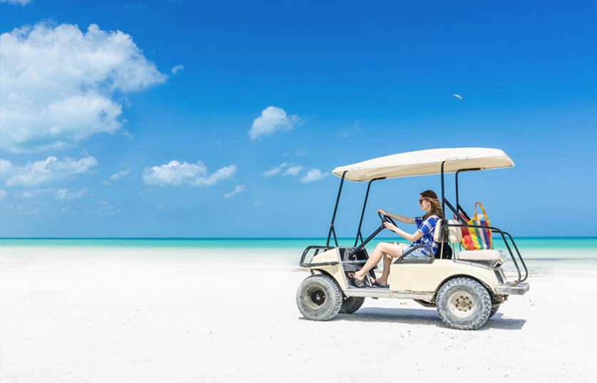 a golfcart riding on the beach
