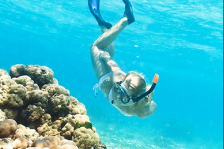 a girl snorkeling next to coral