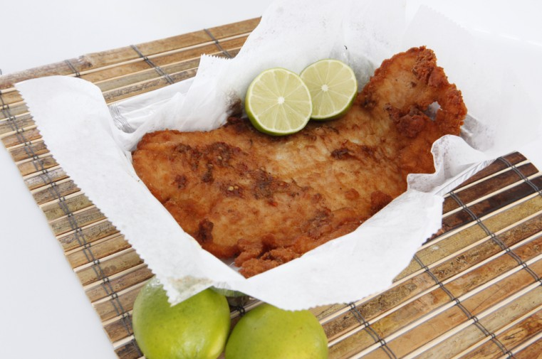 fried fish close up with cut limes on it