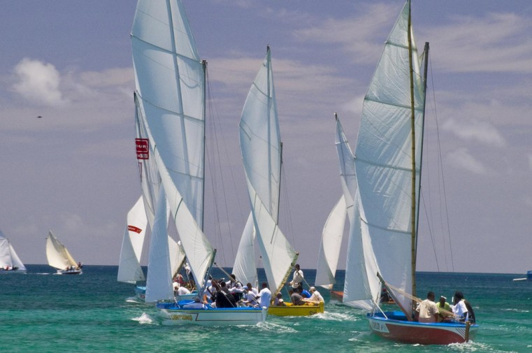 sailboats with people on them in the ocean