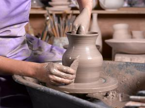 a person making pottery on a wheel