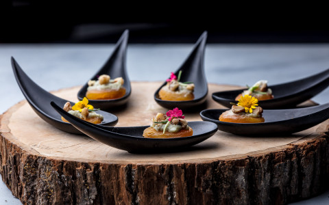 cheese crackers garnished with a small flower on individual black teardrop spoons on a rustic wooden slab