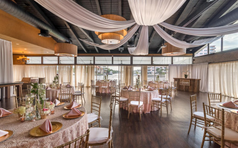 wedding reception dining tables draped with light pink tablecloths, gold plates and pink napkins on the table, and white curtains draping from the ceiling