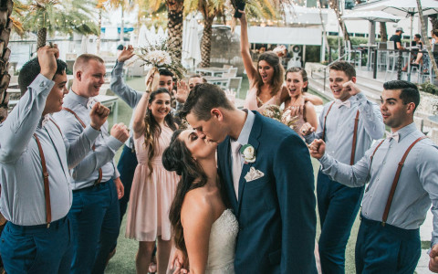 a bride and groom kiss as their bridal party cheers behind them
