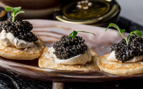 three crackers topped with cream cheese, caviar, and an herb garnish