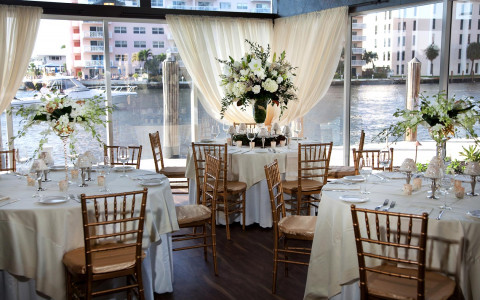 circular dining tables draped with white tables cloths decorated for an elegant wedding with a view of a boat cruising on the intracoastal from the large windows
