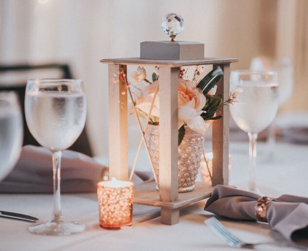 a light pink flower table centerpiece in a sparkly vase under a lantern with water wine glasses and gray napkins on the table