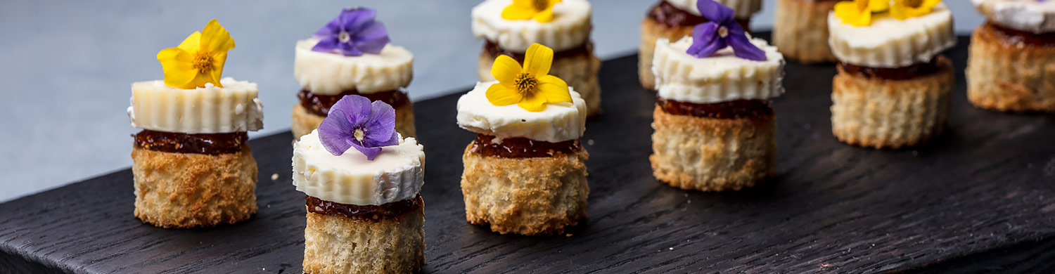 small pastry appetizers on a plate garnished with yellow and purple flowers