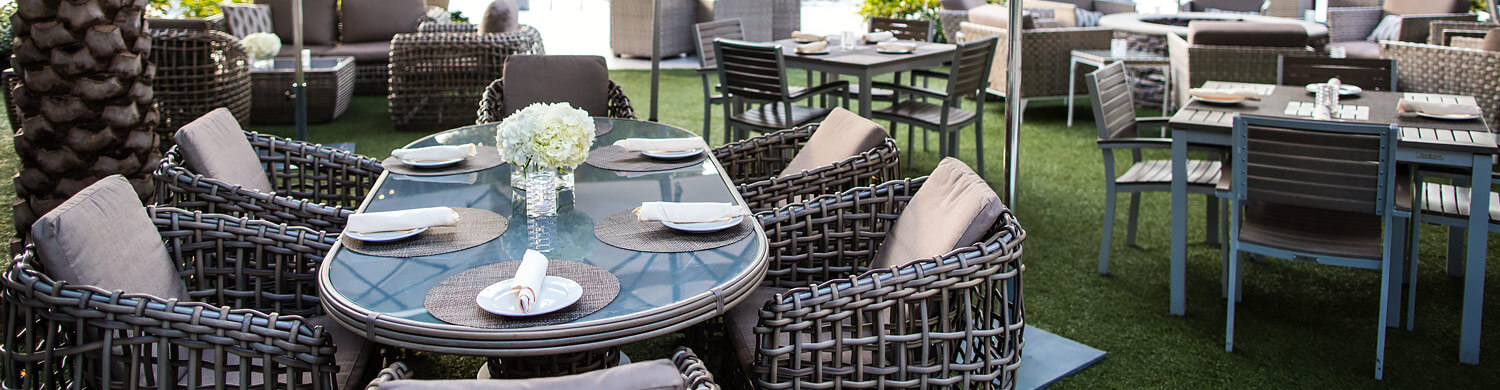 a long rounded glass outdoor dining table set surrounded by cushioned wicker chairs on a grass patio