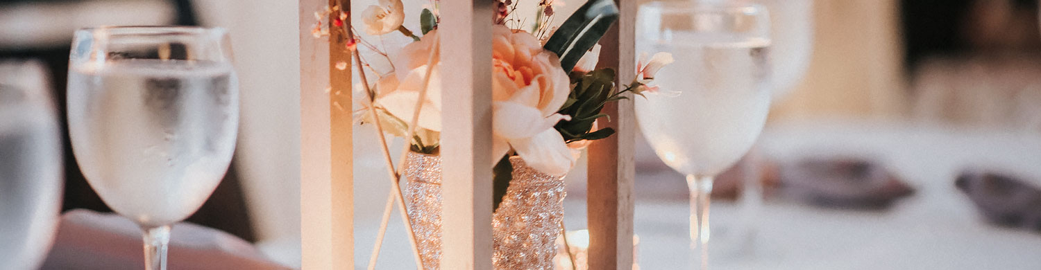 close up of a light pink flower table centerpiece in a sparkly vase under a lantern