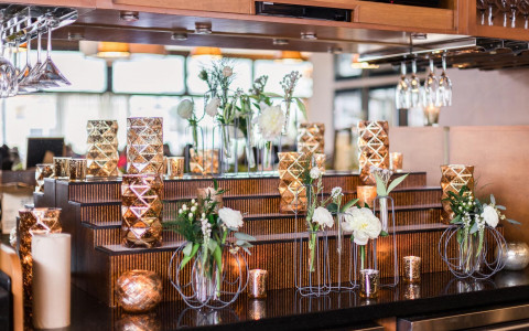 gold vases, white flowers, and gold candles on a table in front of a bar