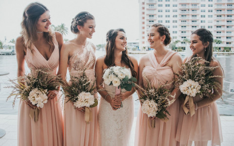 a bride standing with her four bridesmaids in light pink dresses holding flowers